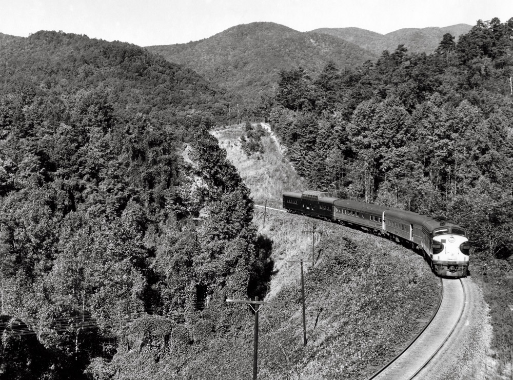 Streamlined diesel locomotive with passenger train in mountains