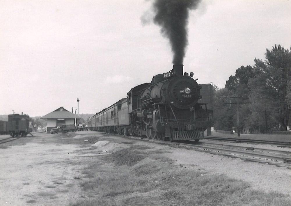 Steam locomotive with passenger train departing station