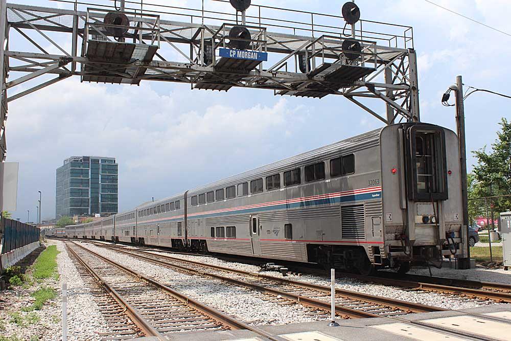 Passenger train passing under overhead signal bridge on multi-track route