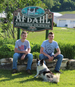 Bo and Ian Afdahl sit in front of an Afdahl Farm sign.