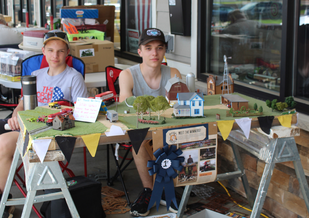 Ian and Bo sit posed behind their model layout.