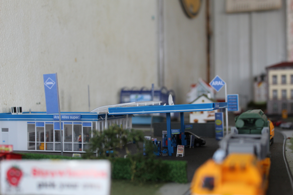 Gas station with vehicles pulled alongside it.