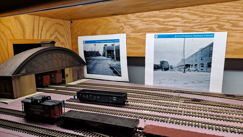 HO scale freight house set into place on layout with reference photos taped to the backdrop support behind