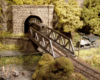A Pennsylvania Railroad diesel switcher emerges from a tunnel onto a pony truss bridge above a road and creek