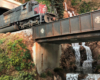A heavily weathered Southern Pacific diesel locomotive emerges from a tunnel onto a plate girder bridge over a waterfalling creek