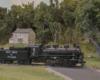 An 0-6-0 steam locomotive pulls a modern boxcar across a road crossing in front of a fieldstone farmhouse