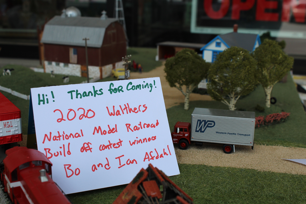 """Placard resting on a model layout that says, """"Hi! Thanks for coming! 2020 Walthers National Model Railroad Build off contest winners Bo and Ian Afdahl."""