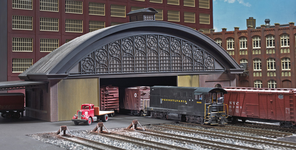 HO scale model of arched roof freight house with Pennsylvania Railroad switcher and boxcars