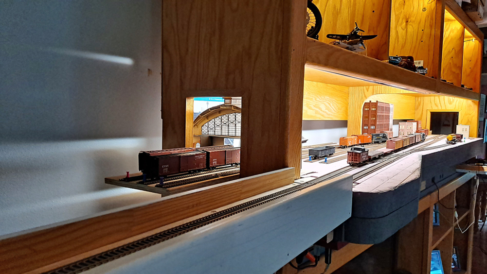End view of layout with staging cassette in foreground, opening in end of entertainment center for freight house
