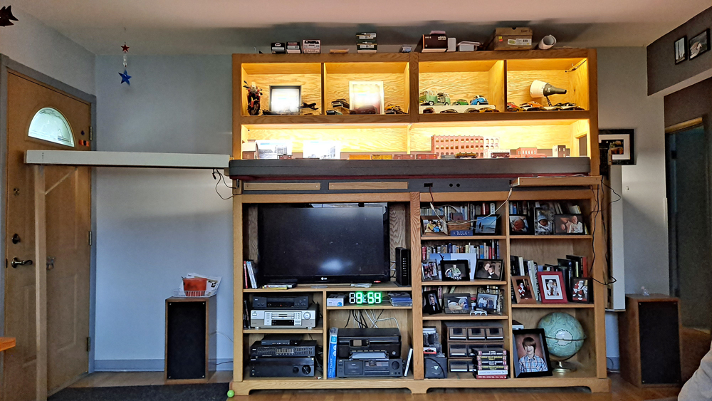 Entertainment center with lighted shelf layout in top half, staging cassette attached to left side