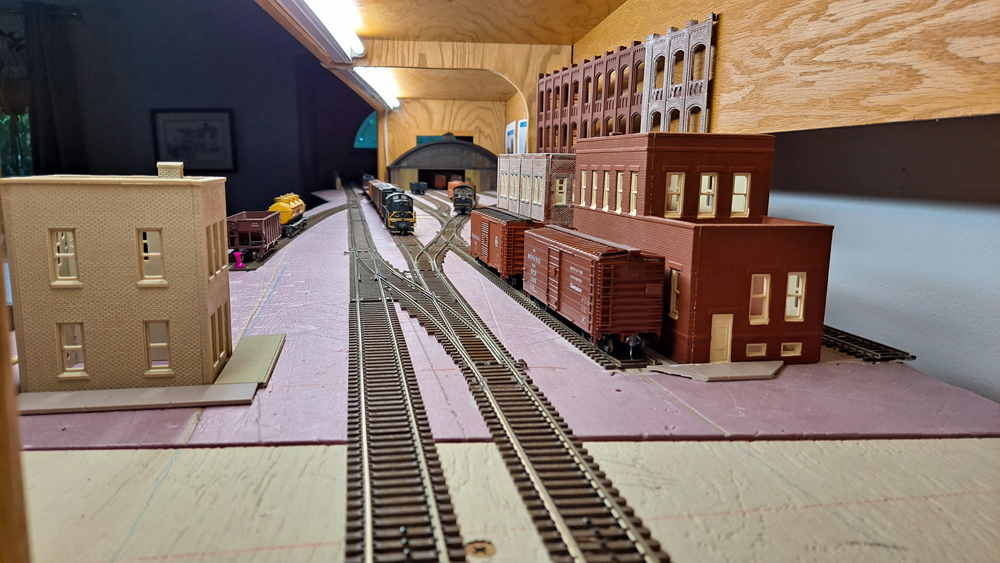 HO scale two track main line with siding on right in front of brick buildings