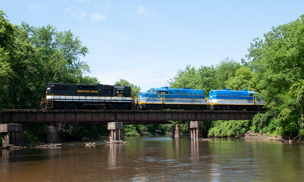 Black and white locomotive pulls two blue and white locomotives as train crosses bride