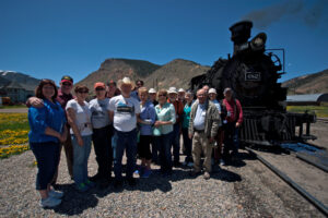A Trains tour group poses next to a narrow gauge steam locomotive in Silverton, Colorado.