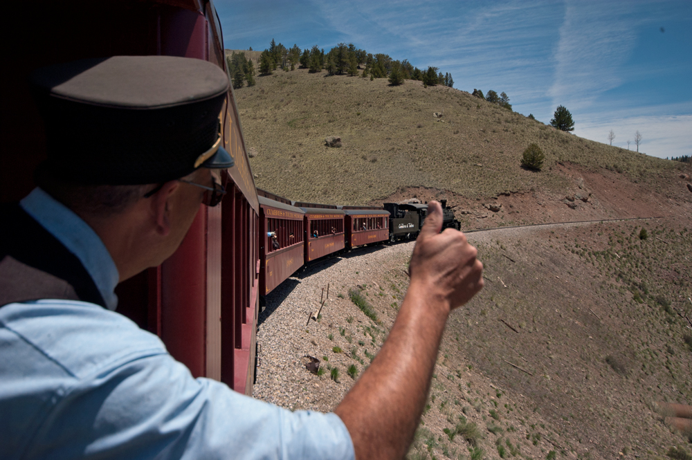 A man in a railroad uniform signals a locomotive crew with the thumbs up sign.