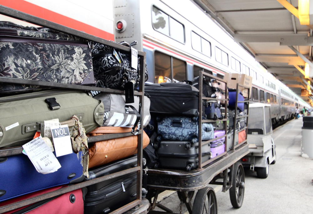 Baggage wagons packed with luggage next to train