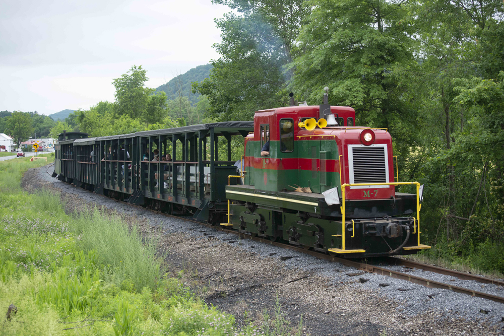 Red and green center-cab diesel hauls passenger train