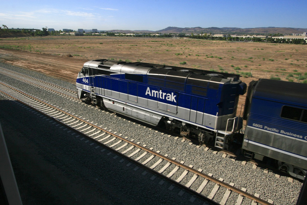 Blue and silver locomotive moves away from viewpoint above tracks