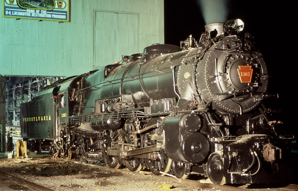 Steam locomotive outside shop building at night