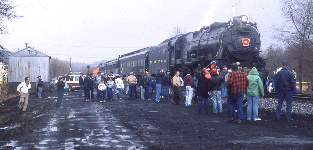 Steam locomotive with short train, surrounded by people