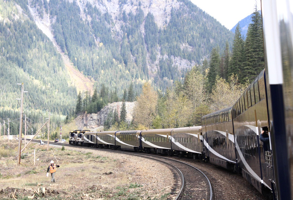 Passenger train rounds curve with Rocky Mountains in background