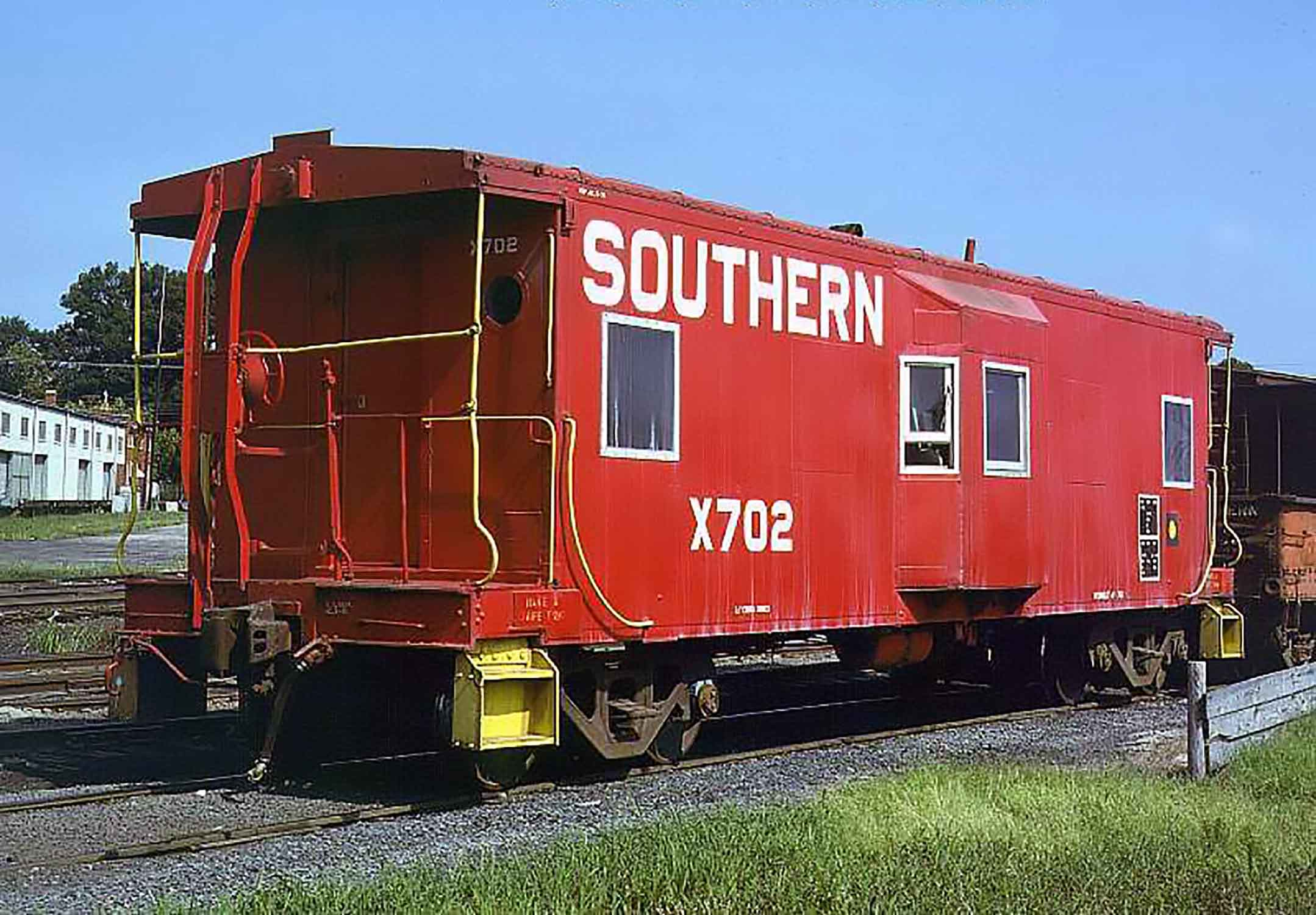 Read bay window caboose on railroad tracks under a blue, cloudless sky in daytime.