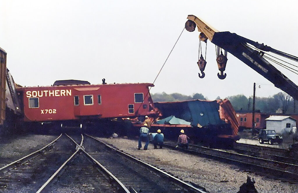 A red caboose sitting perpendicular over railroad track tied to a crane on an overcast day.
