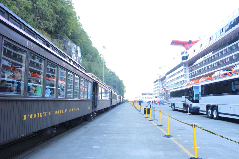 Train with wooden passenger cars waits on dock across from cruise ship