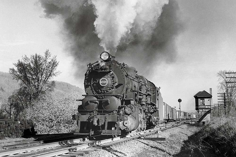 Smoking steam locomotive passes interlocking tower with train