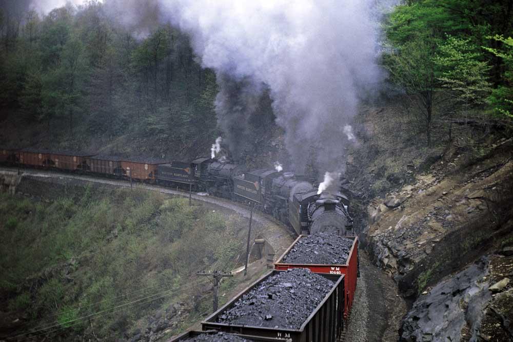 Steam locomotives on a coal train rounding a curve on a hillside