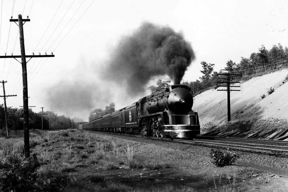 Streamlined steam locomotive with passenger train at speed