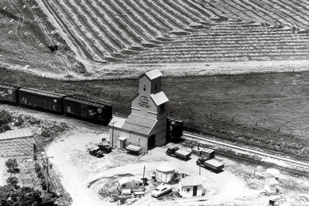 Aerial view of boxcars loading at wooden grain elevator