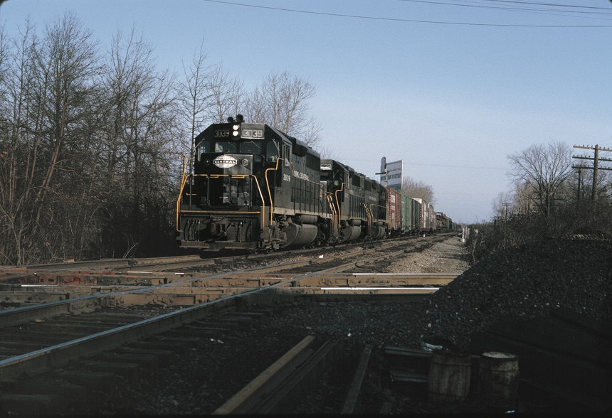 Black diesel locomotives haul freight train toward diamond crossing