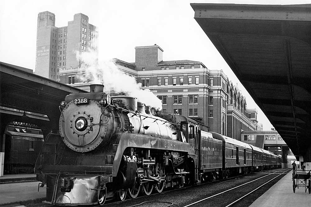 Steam locomotive with passenger train standing in station