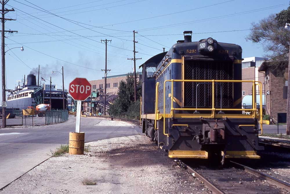 Blue diesel switcher locomotive by Great Lakes carferry boat