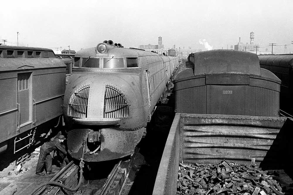 Streamlined passenger train in service yard among older equipment