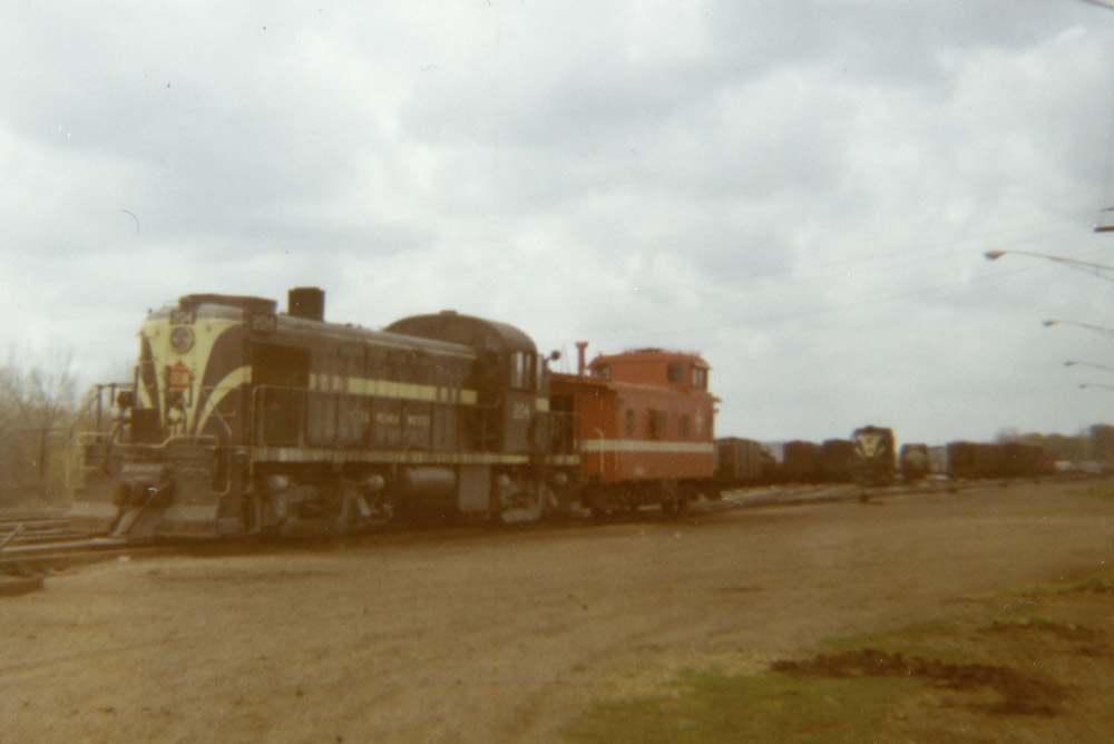 A diesel-electric locomotive and caboose at the end of a rail yard on a cloudy day.