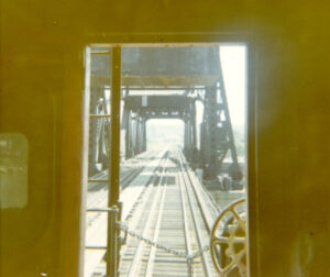 Bridge structures and a double-track appear outside of a caboose door.