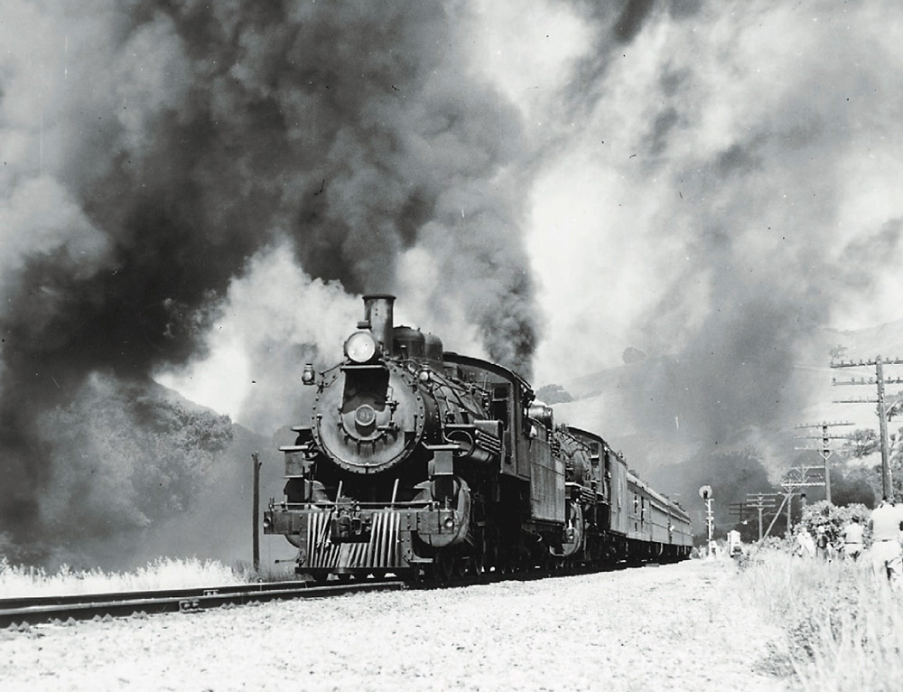 Doubleheaded steam locomotives making smoke during a photo run-by for railfans.