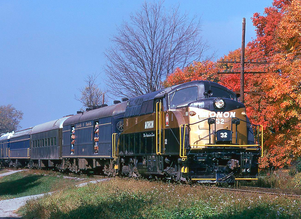 Black and gold diesel locomotive with passenger train