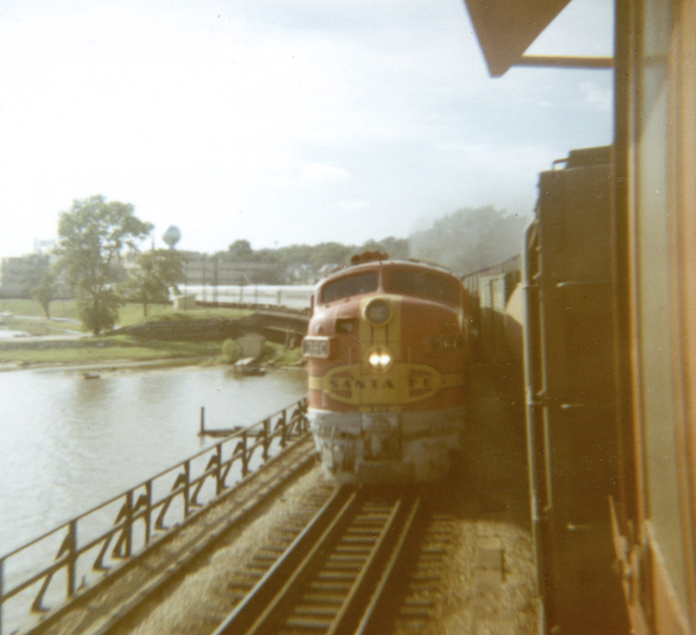 Red-and-yellow diesel-electric locomotive with double-headlight approaches the camera pulling a silver train.