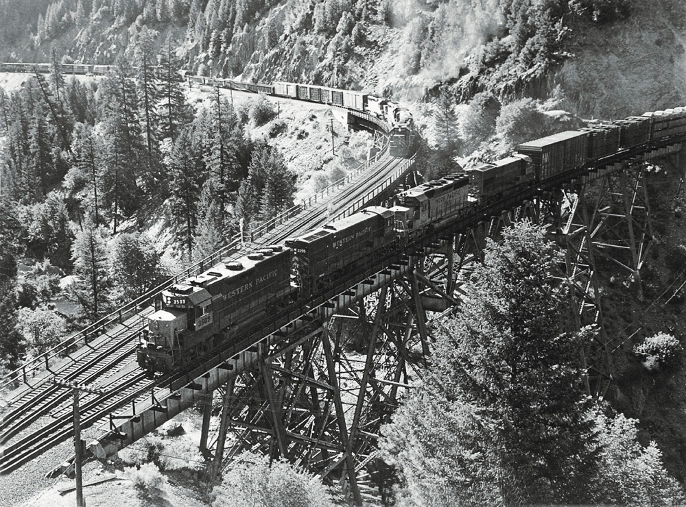 Road-switcher diesel locomotives with freight trains on trestles where two lines converge in mountains