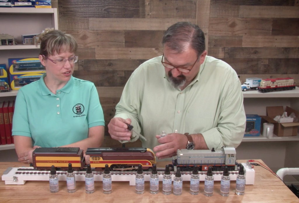 Two people with toy trains apply smoke fluid to a model steam locomotive.