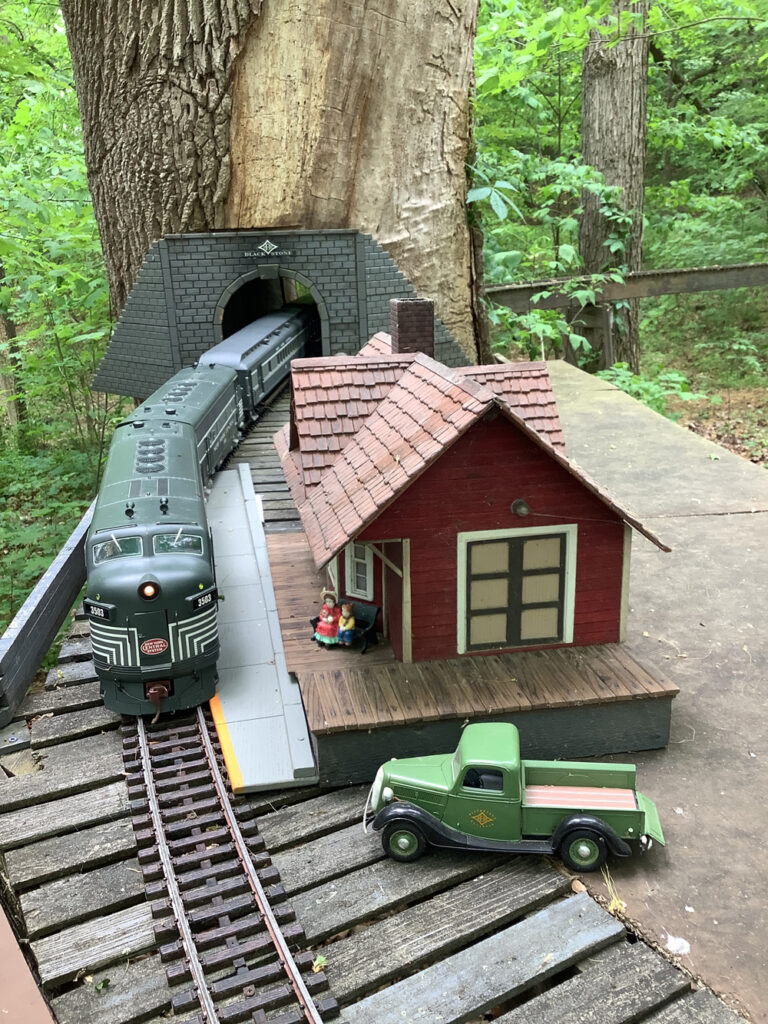 Tunnel through tree with locomotive on track and station