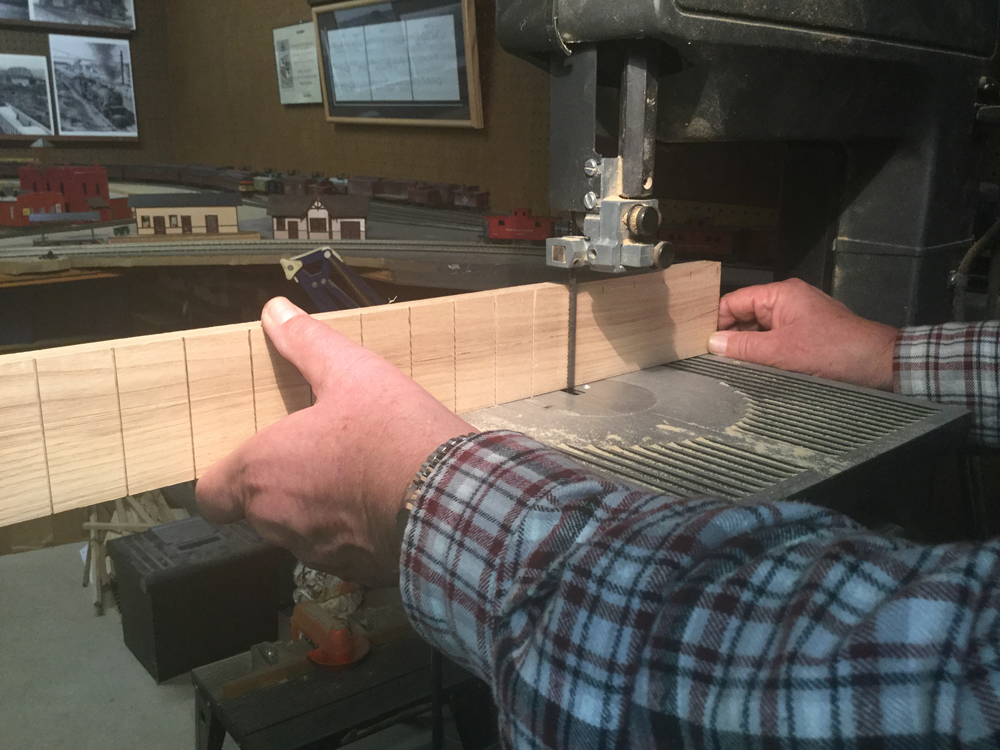 Hands holding a piece of wood at a band saw