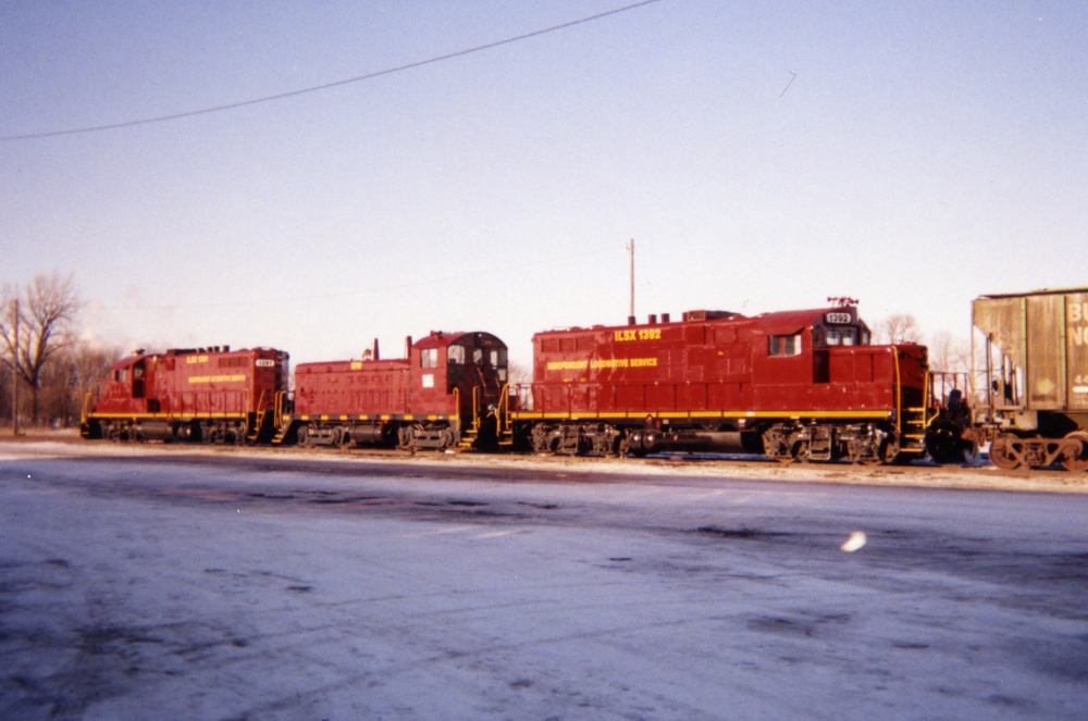 Two four-axle road locomotives frame an end-cab switcher in a snow-covered railroad yard.