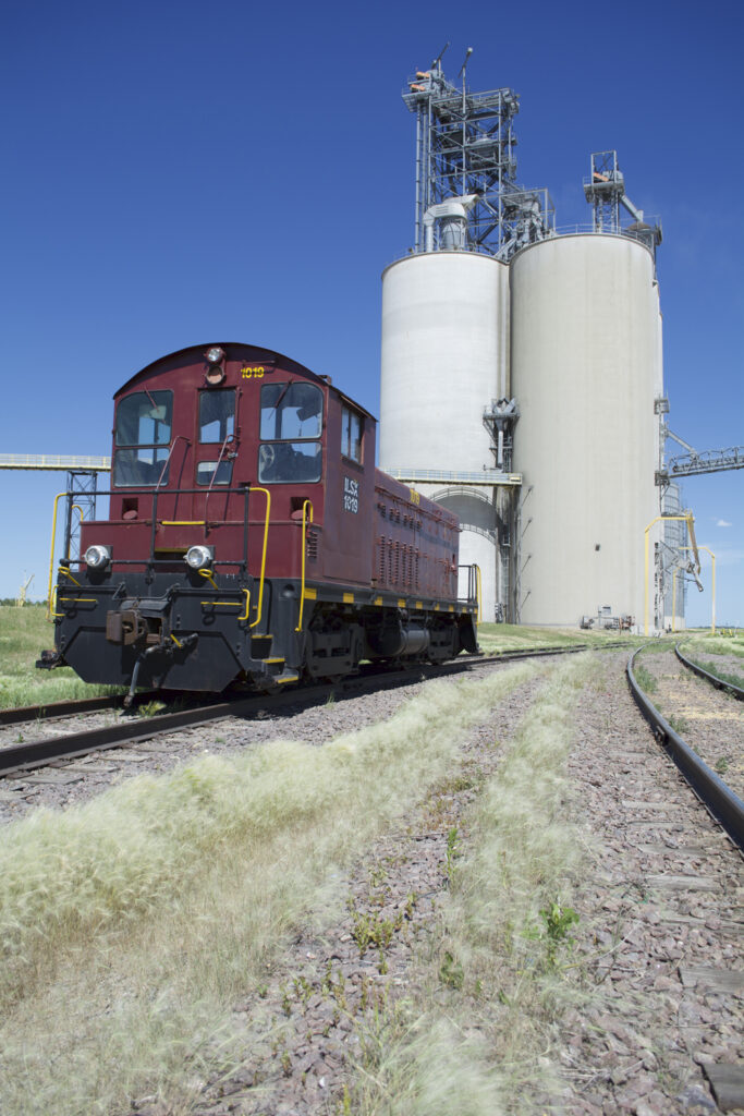An end-cab switcher painted maroon and black on a siding next to a grain elevator complex.