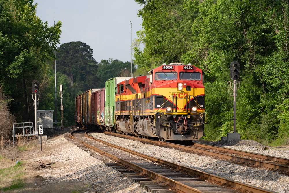 Red, yellow, and black diesel locomotives bring a freight train around a curve and between signals