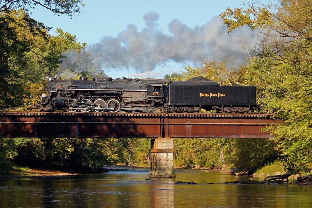 Steam locomotive crosses waterway on bridge