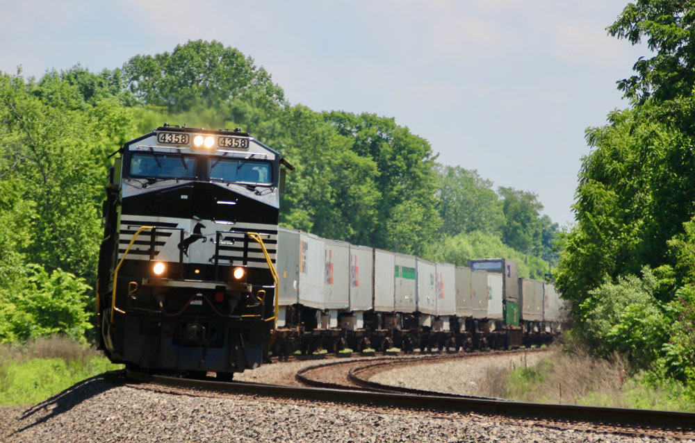 Black locomotive with train of trailers in the Midwest