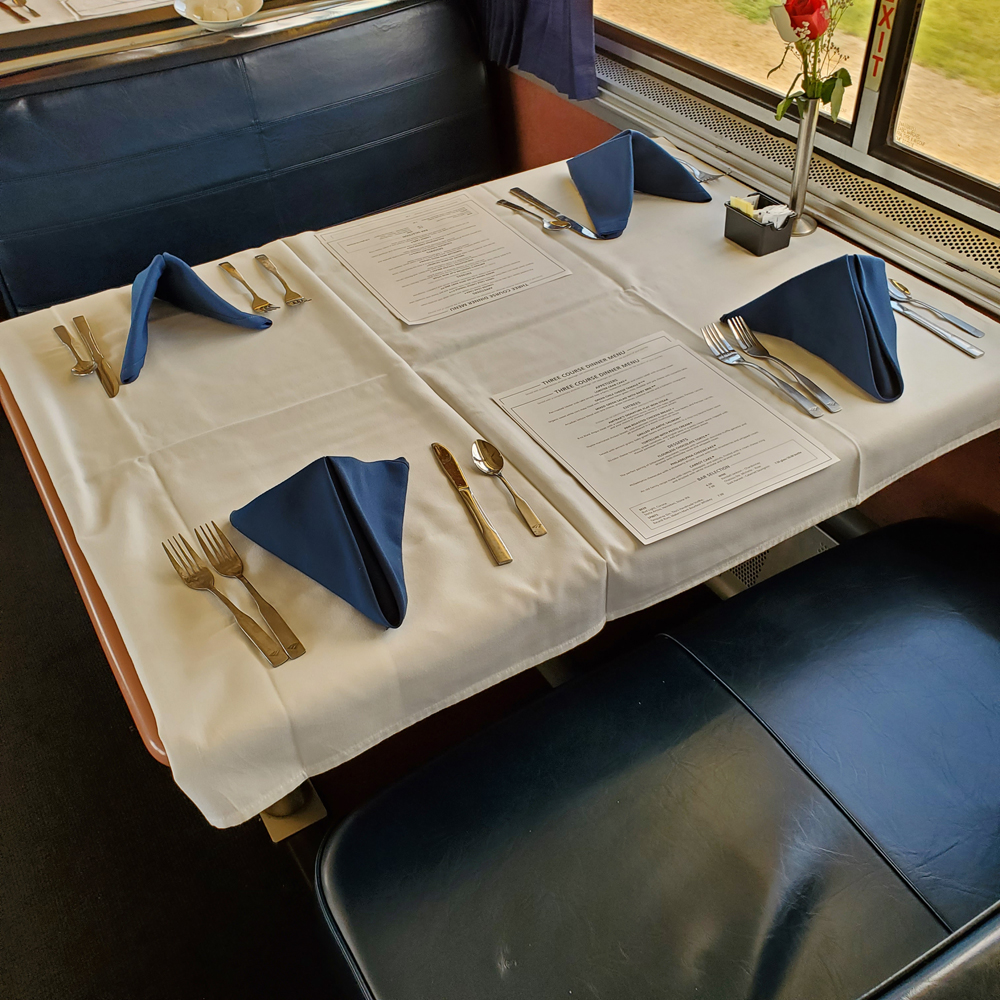 Table with white linen tablecloth and four place settings